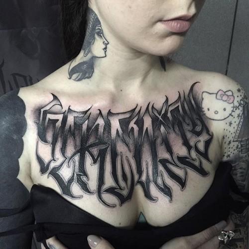 Black ink chest tattoo of mystical ambigram