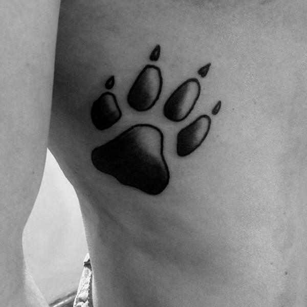 Black ink detailed side tattoo of animal paw print