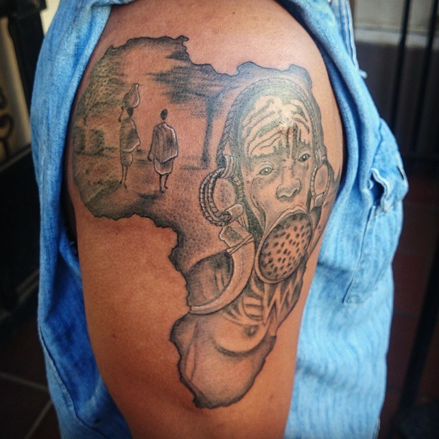 Black ink shoulder tattoo of Africa continent with tribal people