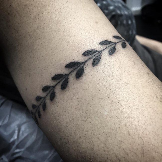 Black ink tattoo of bracelet shaped plant