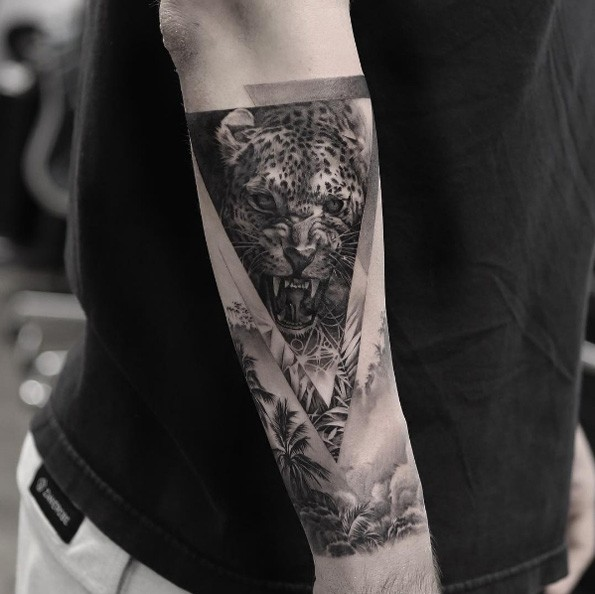 Black ink triangle shaped arm tattoo of leopard portrait with jungle forest