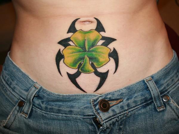 Black tribal with irish clover tattoo on stomach