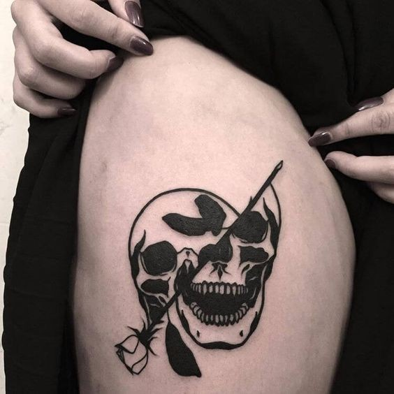 Blackwork style cool looking thigh tattoo of human skull with black rose