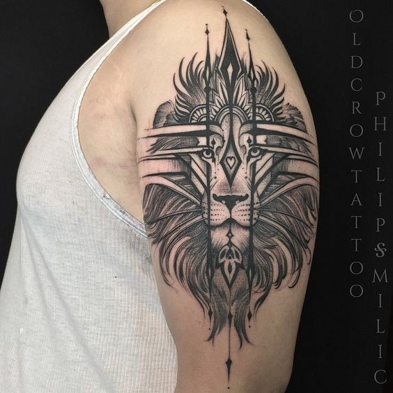 Blackwork style cool looking upper arm tattoo of lion head with cool ornaments