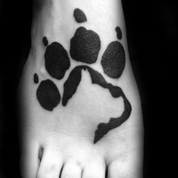 Blackwork style simple looking leg tattoo of paw print