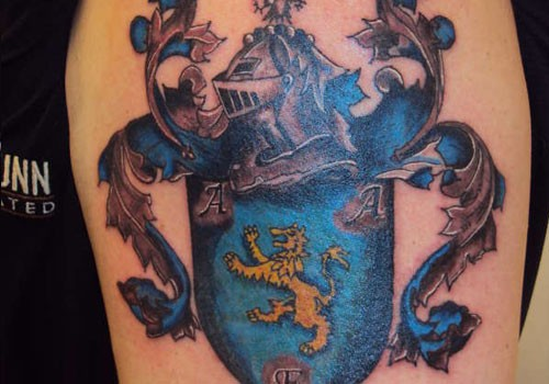 Blue family crest tattoo on shoulder