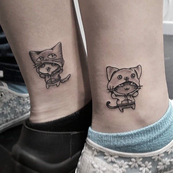 Cartoon style cute looking ankle tattoo of funny cats