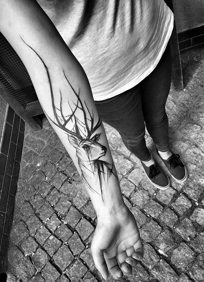 Cartoon themed black ink forearm tattoo of crying deer by Inez Janiak