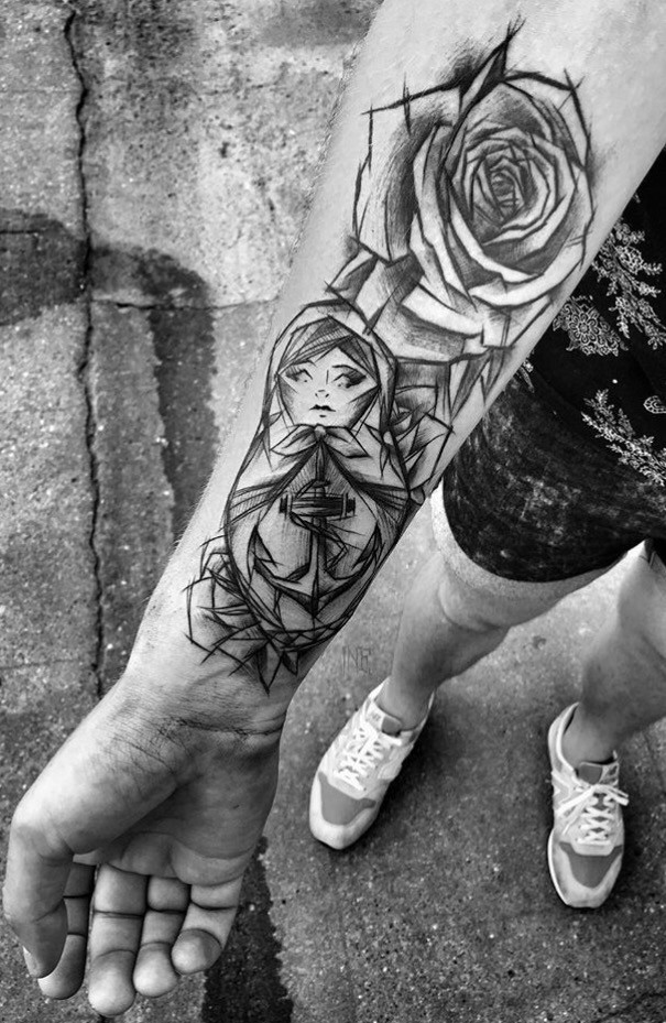 Cartoon themed black ink painted by Inez Janiak forearm tattoo of Matryoshka doll with rose