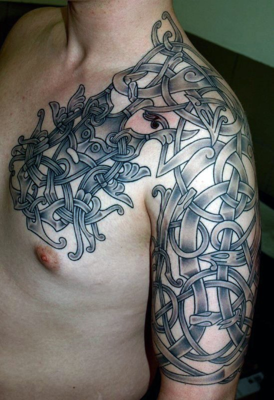 Celtic style black ink shoulder and chest tattoo of various ornaments