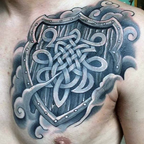 Celtic style colored chest tattoo of big shield with emblem