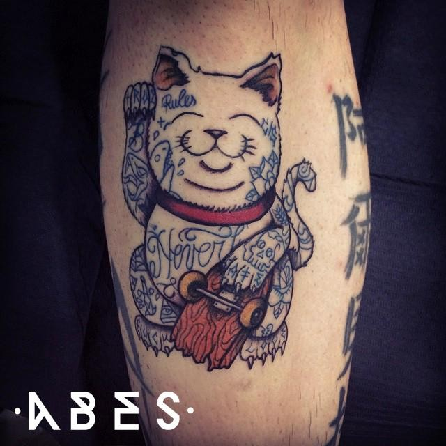 Colored amazing looking leg tattoo of funny maneki neko japanese lucky cat with broken skate