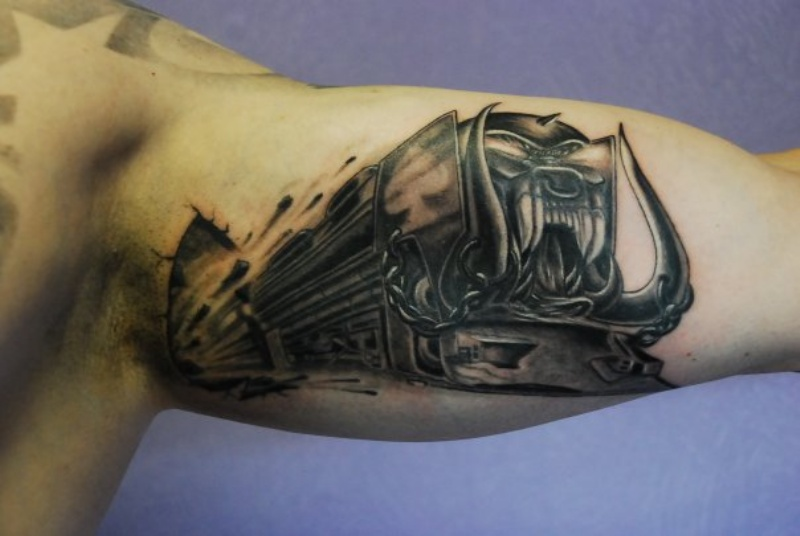 Colored black and gray biceps tattoo of demonic train