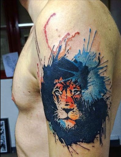 Colorful lion's head tattoo on shoulder area in watercolor style