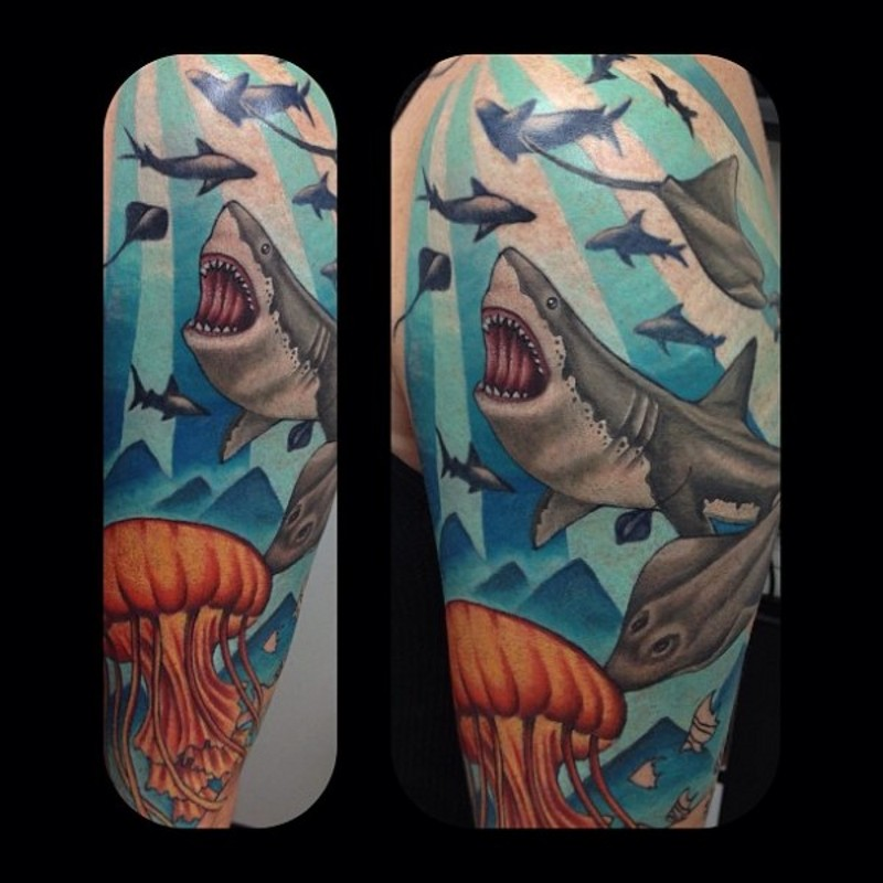 Colorful underwater life tattoo on shoulder stylized with sharks and jellyfish