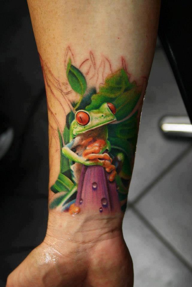 Coloured little green frog tattoo on wrist