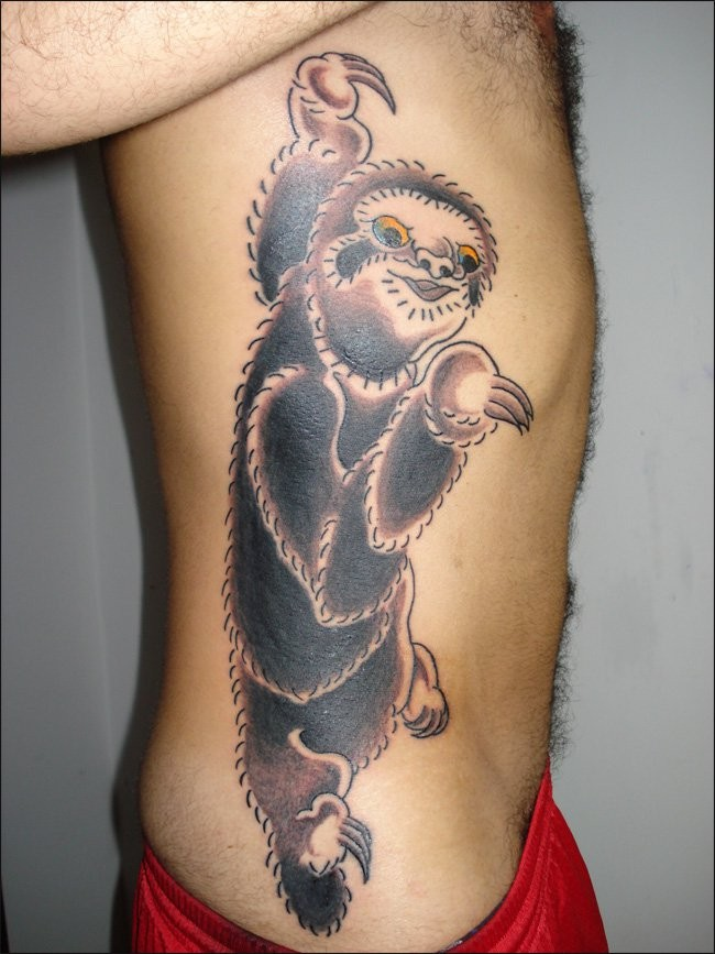 Coloured sloth with orange eyes tattoo on ribs