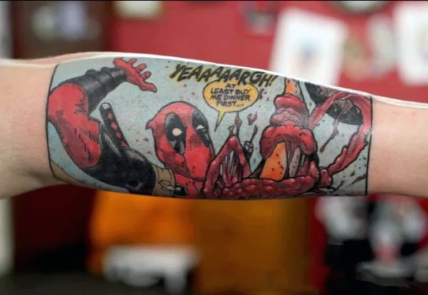 Comic books style colored arm tattoo of funny Deadpool with lettering