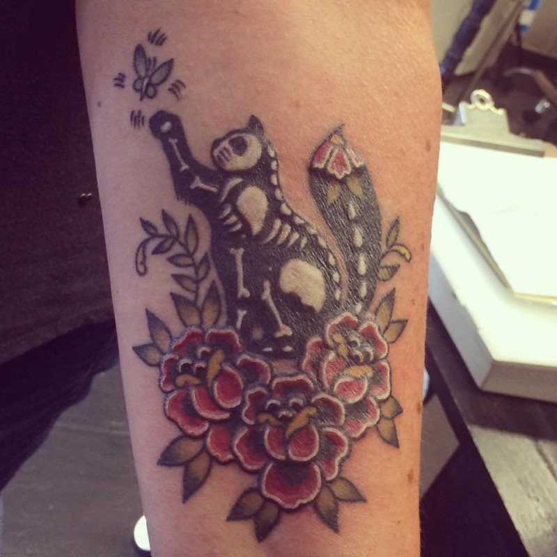 Cool illustrative style arm tattoo of cat with skeleton and flowers