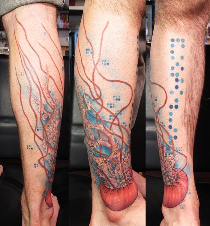 Creative red jellyfish in water tattoo on leg