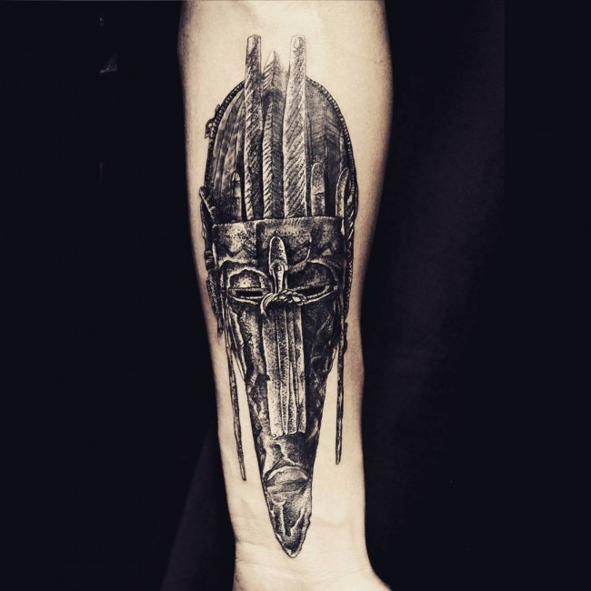 Creepy and mystical looking arm tattoo of ancient tribal mask