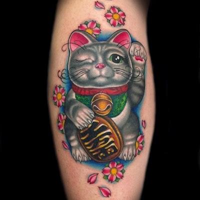 Cute and funny looking leg tattoo of colored maneki neko japanese lucky cat tattoo on leg