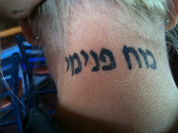Cute black hebrew tattoo on neck