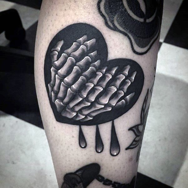 Cute looking black ink leg tattoo of heart with skeleton hands