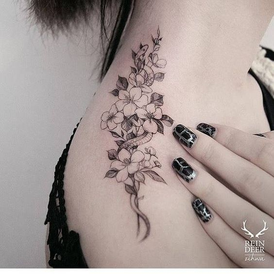 Cute looking blackwork style shoulder tattoo of small snake and flowers by Zihwa