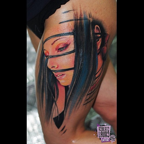 Detailed and colored thigh tattoo of tribal woman face