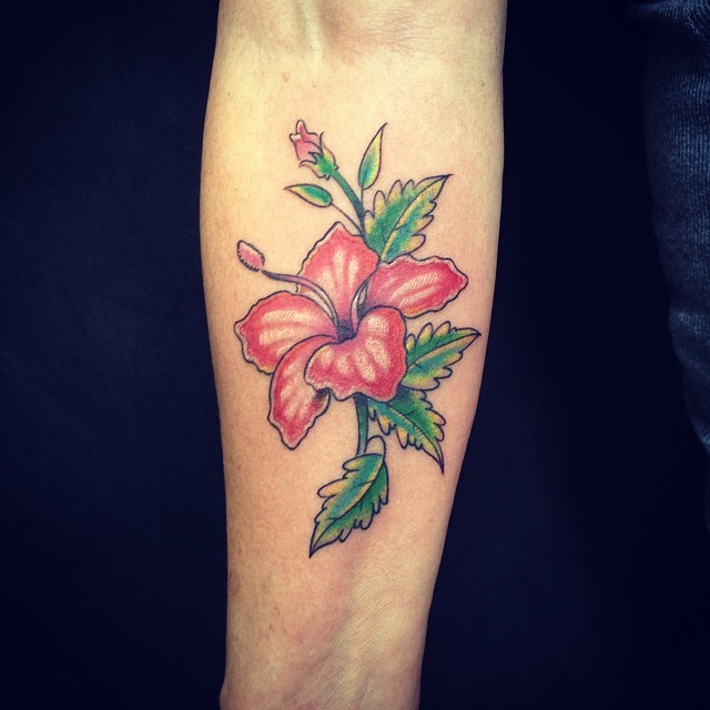 Detailed colored hibiscus flower tattoo on forearm in Hawaiian style