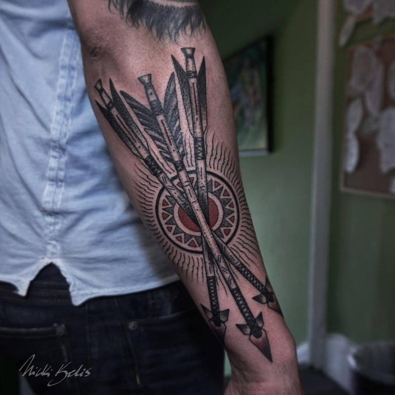 Detailed looking colored arm tattoo of crossed arrows with sun
