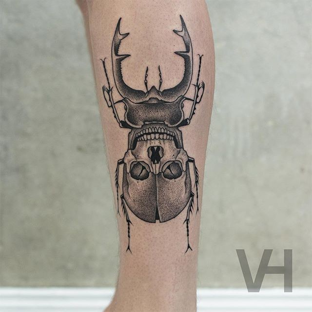Dot style cool looking arm tattoo of big bug stylized with human skull