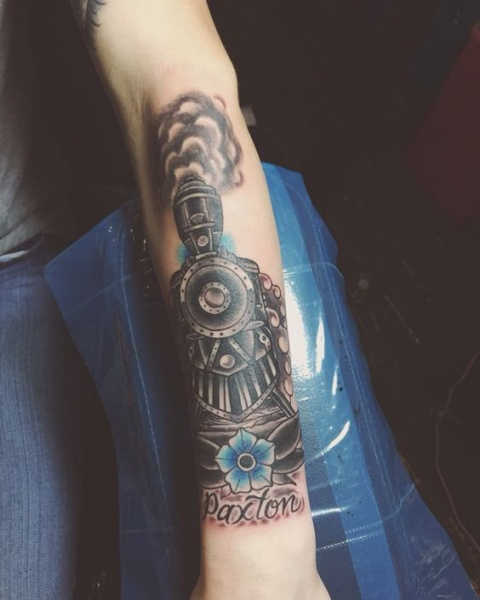 Dramatic memorial colored arm tattoo of train with flower and lettering