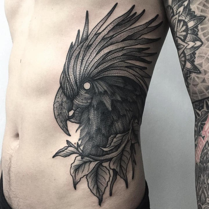 Engraving style black ink side tattoo of parrot with leaves