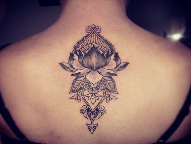 Engraving style black ink upper back tattoo of lotus flower with ornaments by Caro Voodoo
