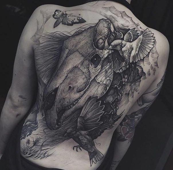 Engraving style black ink whole back tattoo of dinosaur skull with birds and butterfly