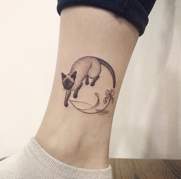 Engraving style interesting looking ankle tattoo of cat with flowers