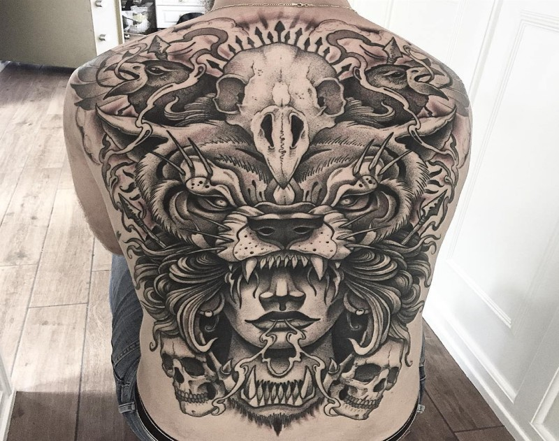 Enormous mystical whole back tattoo of ancient man with animal skull helmet
