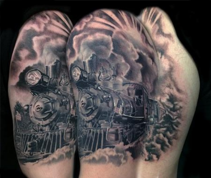 Enormous very detailed upper arm tattoo of train with clouds of steam