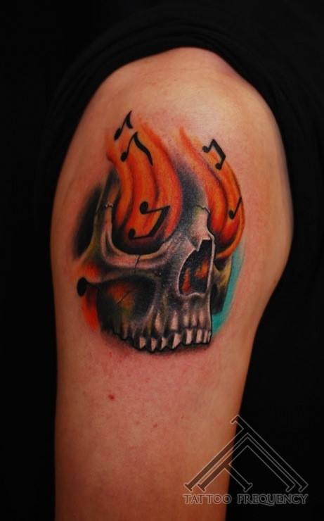 Fantastic designed little colored music skull with flames tattoo on shoulder