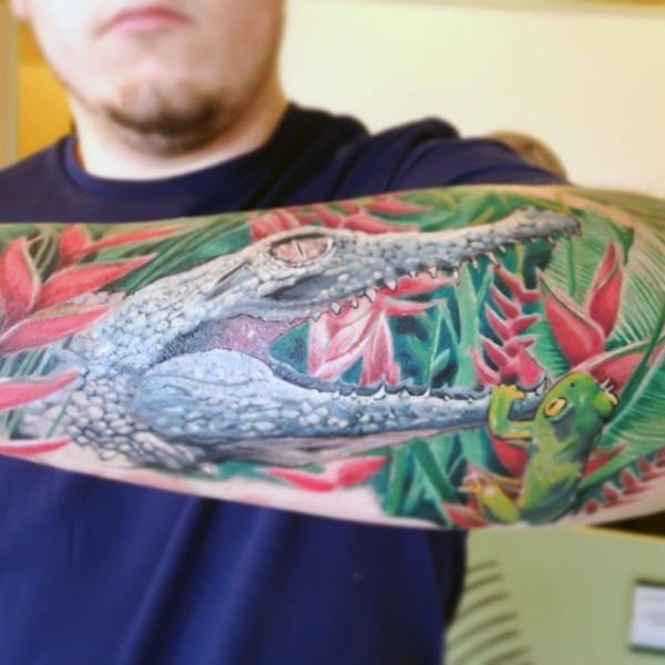 Fantastic natural looking colored little alligator with frog tattoo on arm