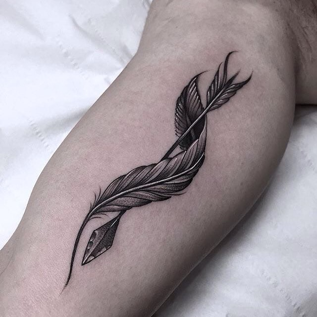 Feather curled around arrow tattoo on biceps