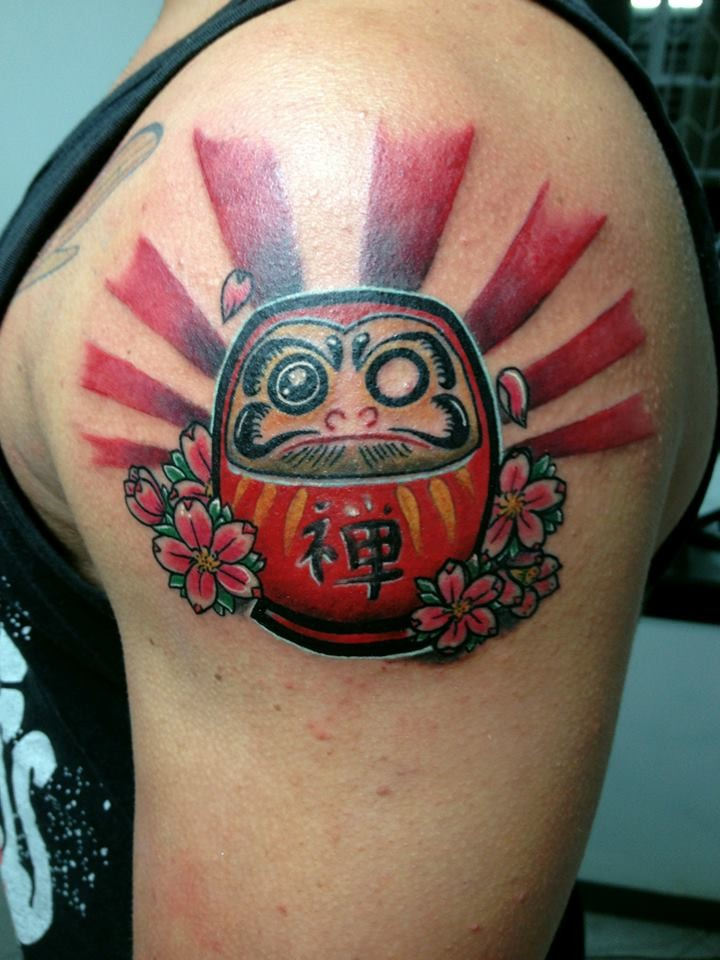Funny cartoon style colored shoulder tattoo of daruma doll with flowers