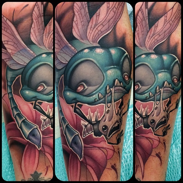 Funny designed cartoon like evil dragonfly tattoo on forearm with flower
