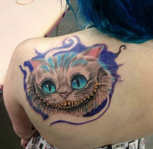 Funny fairy tale smiling Cheshire cat colored detailed upper back tattoo with violet paint shadow
