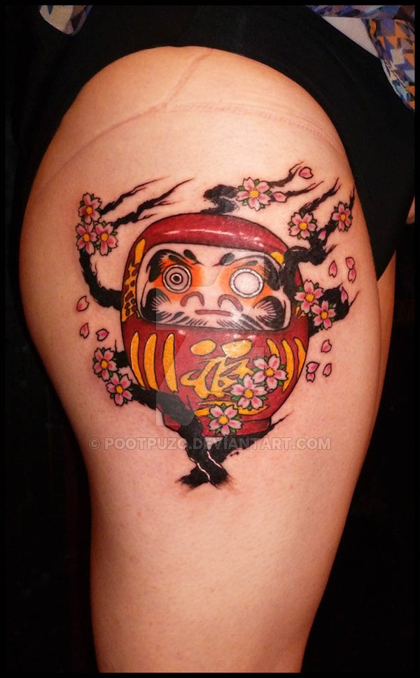 Funny looking colored thigh tattoo of daruma doll with blooming tree
