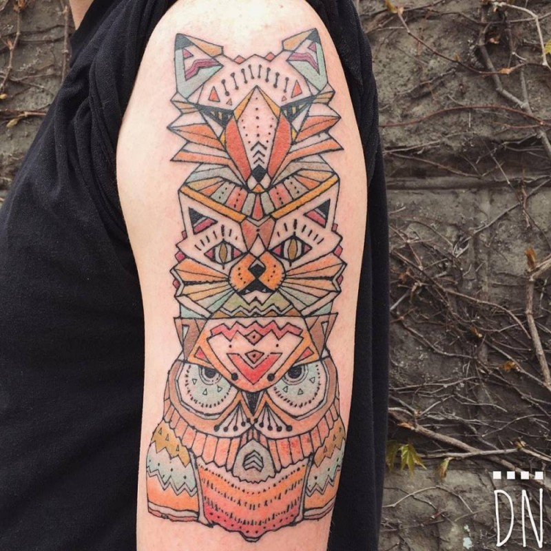 Geometrical style colored upper arm tattoo of old totem