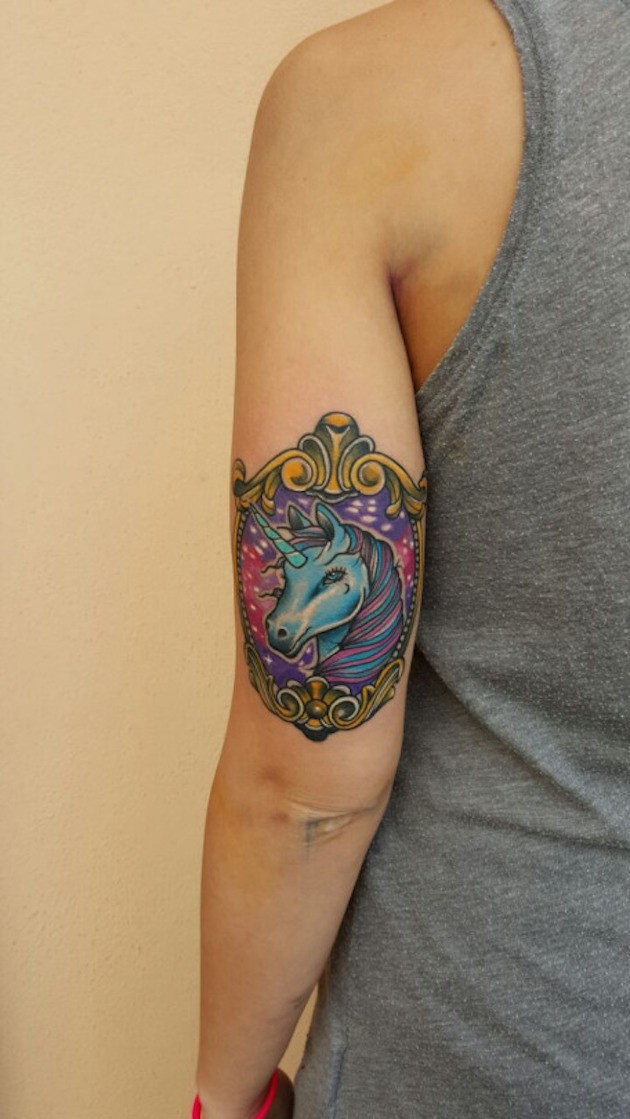 Gorgeous fairy tale colored unicorn in old style frame tattoo on biceps