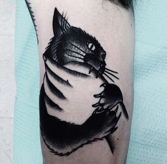 Homemade style black ink arm tattoo of hand holding hat